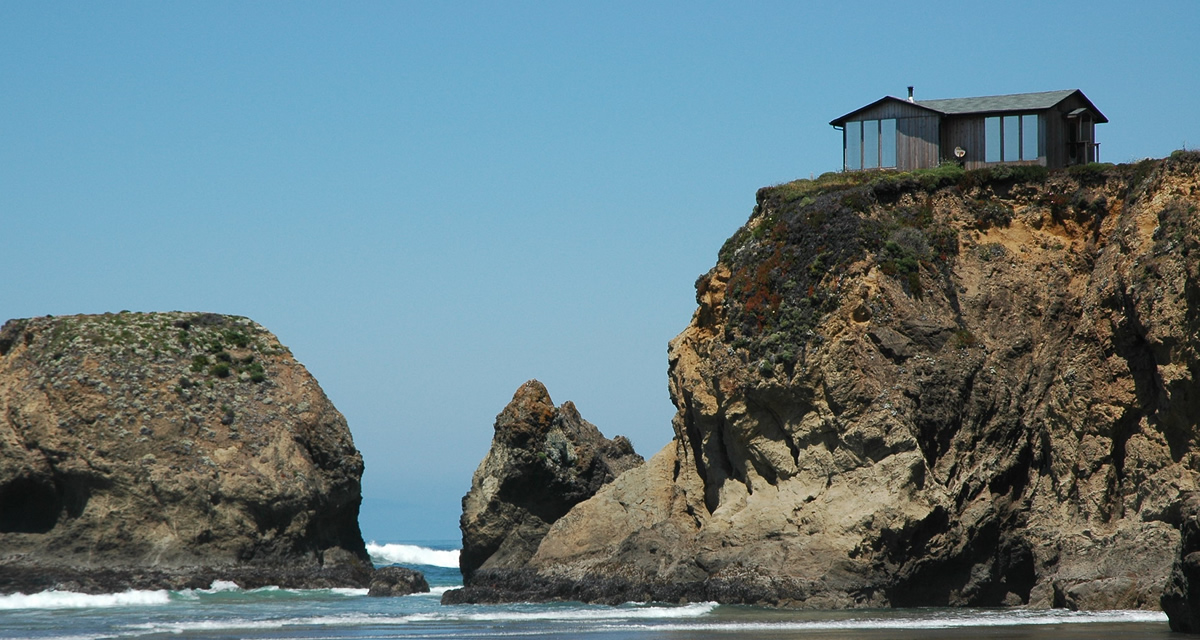 house on top of a rock with ocean below