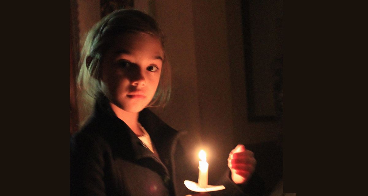 young girl holding candle